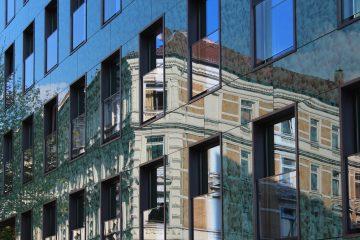 Ein Gebäude spiegelt sich in einer Glasfassade.