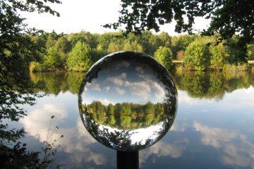 Ein blick in die Glaskugel wo sich Wasser, Bäume und Himmel spiegeln.