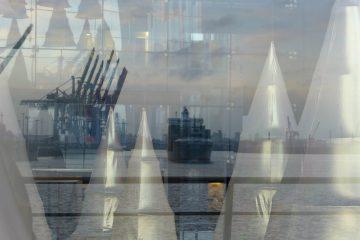 Hamburg, 2015. Stilisierte Weihnachts-bäume glänzen im Innern. Außen spiegelt das Fenster Hafen, Schiff und Elbe.
