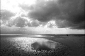 Wolken ziehen sich zu am Strand in Schwarz Weiß.