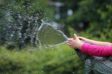 Kinderhände spielen mit einem Wasserstrahl.