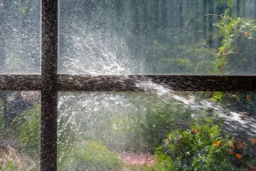 Ein Wasserstrahl trifft auf eine Glasscheibe.