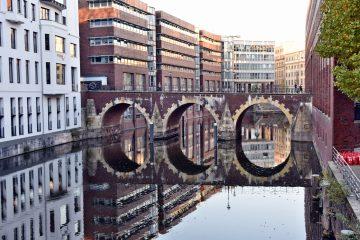 Brückenbögen der Ellerntorsbrücke spiegeln sich im Fleet.