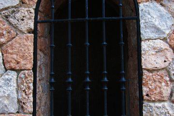 Vergittertes Bogenfenster in attraktiver Naturstein-Fassade.