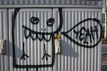 Ein Grafiti auf einem Grauen Kasten.