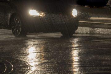 Nachts Im Regen ist ein Auto zu sehen, Scheinwerfer spiegeln sich auf nasser Straße.