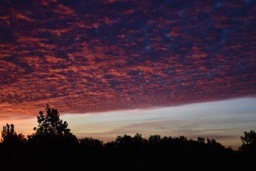 Bei einem Sonnenaufgang ziehen die Wolken vorbei.